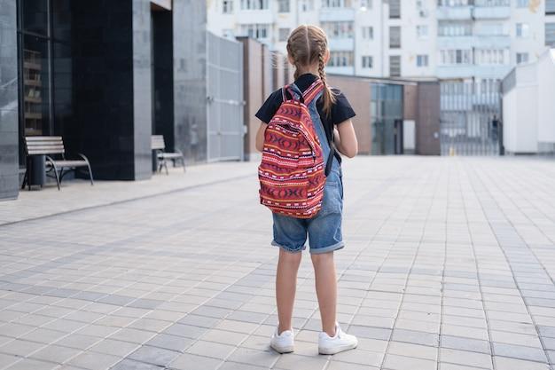 Seltene ansicht eines traurigen mädchens mit rucksack und büchern gehen zur schule. zurück zum schulkonzept.