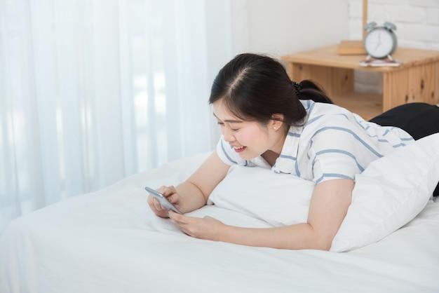 Seltene ansicht oder rückseite der asiatischen frau legte sich auf das bett, hielt smartphone und sah etwas nach