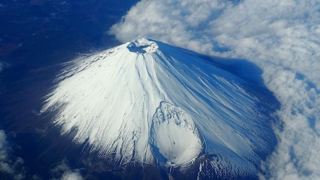 Seltene bilder draufsichtwinkel des berges. fuji berg und weiße schneedecke darauf und leichte wolken und klarer sauberer blauer himmel