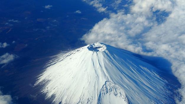 Seltene bilder draufsichtwinkel des berges fuji und weiße schneedecke darauf und leichte wolken und klarer, sauberer blauer himmel, die aus dem flugzeug schießen.