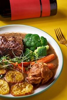 Seltenes roastbeef-essen mit bio-wurzelgemüse und traditionellem yorkshire-pudding mit sauce, gedünstetem gemüse.
