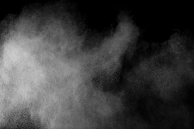 Seltsame formen der explosionswolke des weißen pulvers gegen schwarzen hintergrund