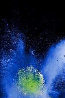 Seltsame formen des blauen pulvers explodieren wolke auf schwarzem hintergrund.