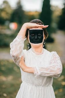 Seltsame frau im hochzeitskleid mit kreativer gesichtskunst, die gesten durch ihre hände im sommerpark zeigt