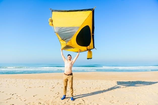 Seltsamer bizarrer glücklicher lächelnder topless mann, der zelt über kopf hält. sonniger morgen am atlantik in portugal.