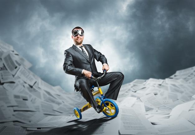 Seltsamer geschäftsmann, der ein kleines fahrrad reitet