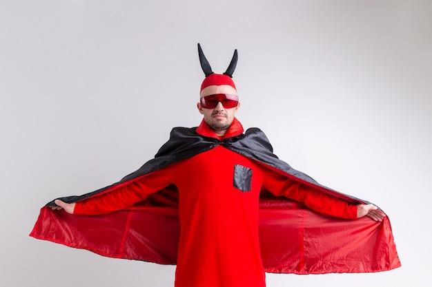 Seltsamer teuflischer mann in der sonnenbrille und im schwarzen roten halloween-kostüm, das aufwirft