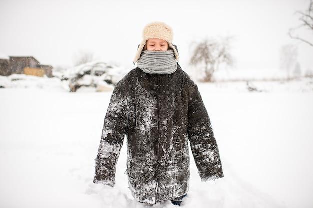 Seltsames kleines mädchen in abgenutzten übergroßen kleidern, die an der verschneiten straße am wintertag im russischen dorf stehen