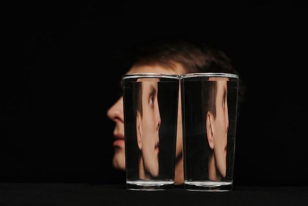 Seltsames porträt eines mannes im profil durch zwei gläser wasser auf einem schwarzen hintergrund