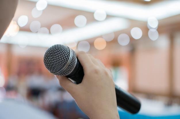 Seminar-konferenz-konzept: rückseite der intelligenten geschäftsfrausprache und sprechen mit dem mikrofon, das im konferenzsaal spricht