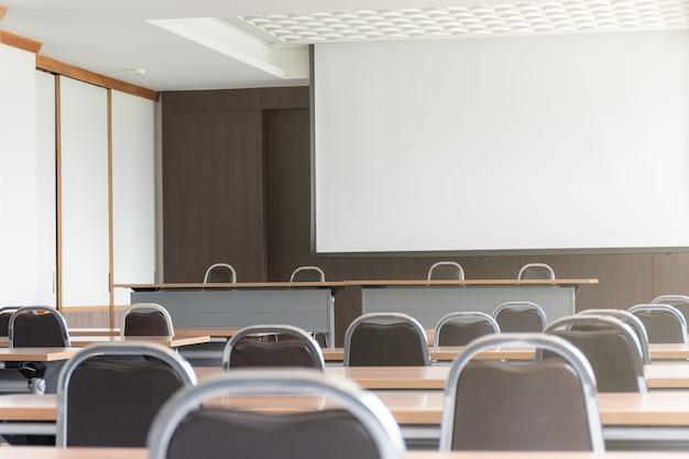 Seminarraum mit rednertisch auf der bühne und whitescreen-hintergrund