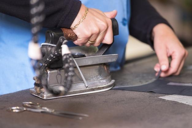 Semstress bügelt den stoff. näherin bügelt fabirc in einer nähwerkstatt.