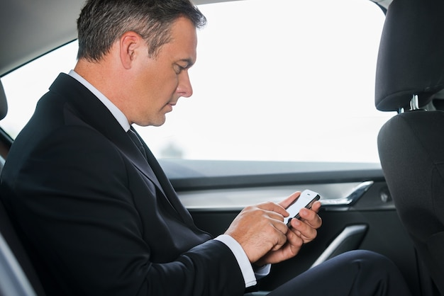 Senden einer dringenden nachricht. seitenansicht eines selbstbewussten reifen geschäftsmannes, der auf dem rücksitz eines autos eine nachricht auf seinem smartphone eingibt