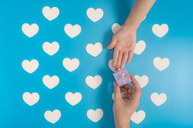 Senden einer geschenkbox auf blau mit weißem herzmuster