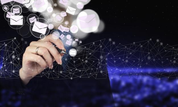Senden von e-mails.massensendungen. hand, die einen digitalen grafikstift hält und ein digitales hologramm zeichnet e-mail- und sms-zeichen auf dunklem, unscharfen hintergrund der stadt. e-mail-geschäftskonzept.