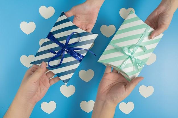 Senden von geschenken, die mit einem band auf blauem hintergrund mit weißem herzen gebunden sind