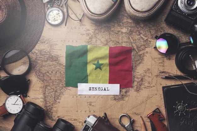 Senegal-flagge zwischen dem zubehör des reisenden auf alter weinlese-karte. obenliegender schuss