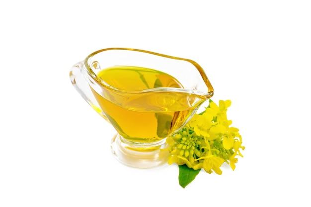 Senföl in einem glassoßeboot, gelbe senfblumen lokalisiert auf weißem hintergrund