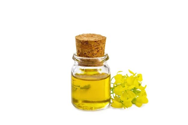 Senföl in einer glasflasche, gelbe senfblumen lokalisiert auf weißem hintergrund