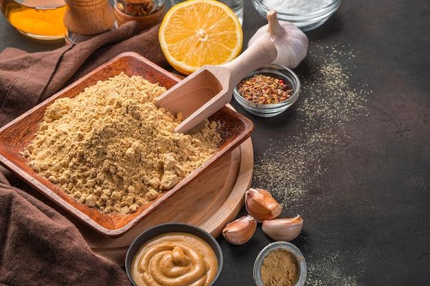 Senfpulver und gewürze auf dunklem hintergrund mit platz zum kopieren. das konzept der kochrezepte.