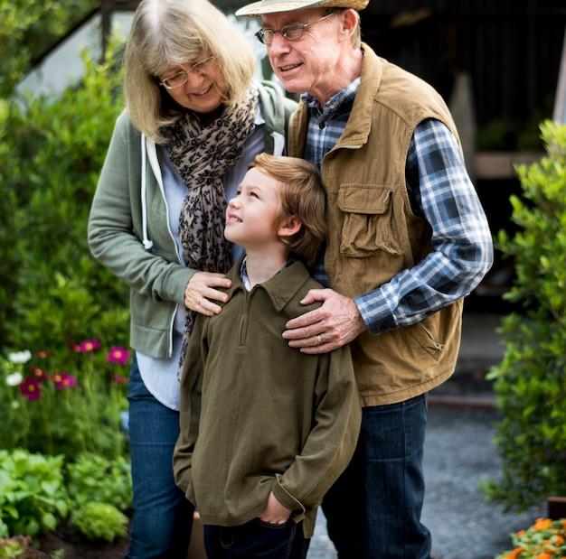 Senio-rcouple mit dem kleinen jungen, der zu hause hinterhof im garten arbeitet