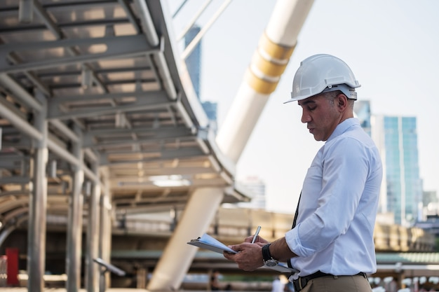 Senior 50s amerikanischer architekt ingenieur manager in schutzhelm schreiben notizen auf papier blaupause in der modernen stadt. baustellenbesichtigung oder überprüfung des projektfortschritts in der stadt.