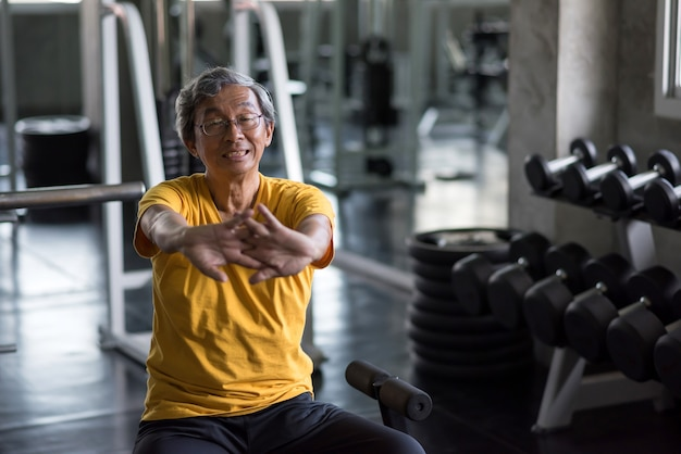 Senior 60er jahre lächelnder mann, der die hände im fitnessstudio ausdehnt