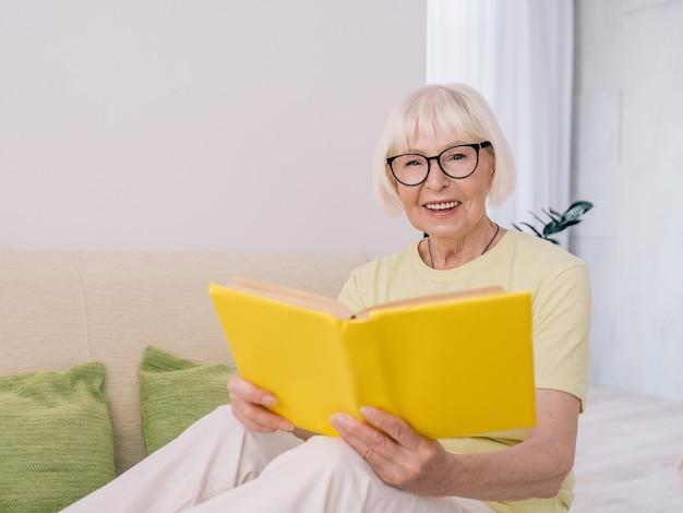 Senior alte frau mit grauen haaren, die zu hause ein buch liest