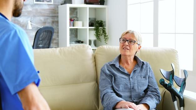 Senior alte frau sitzt auf der couch im pflegeheim im gespräch mit dem arzt. über die schulter geschossen