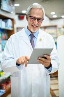 Senior apotheker arbeitet an tablet in seinem geschäft