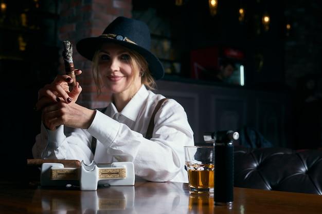 Senior attraktiver weiblicher gangster, der zigarre über dunkelheit im restaurant raucht