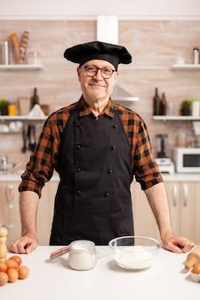 Senior bäcker lächelnd blick in die kamera in der küche pensionierter älterer koch in küchenuniform zubereitung von gebäckzutaten auf holztisch bereit, hausgemachtes leckeres brot, kuchen und pasta zu kochen