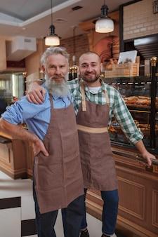 Senior baker und sein sohn lächeln in die kamera und posieren stolz in ihrem familienbäckereigeschäft