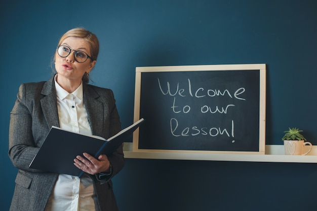 Senior blonde lehrerin unterrichtet vor der klasse in der nähe der tafel mit einem buch