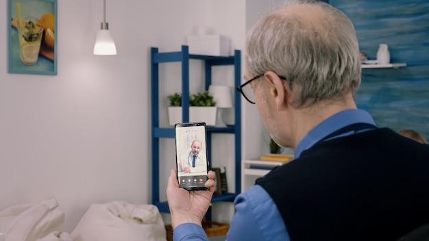 Senior business-mann, der während der videokonferenz mit einem entfernten arzt diskutiert, der smartphone hält. junger arzt, der die medizinische behandlung per videoanruf mit moderner drahtloser technologie erklärt