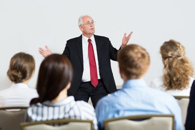 Senior business-mann geben einen vortrag