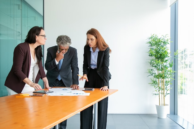 Senior chef in brillen, der statistiken beobachtet und das projekt mit partnern bespricht. inhalt erfolgreiche geschäftsleute, die mit tafeln und papieren in der nähe des tisches stehen und sprechen. geschäft und zusammenarbeit con