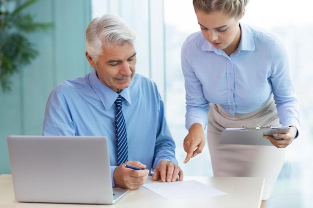 Senior-chef und sekretär dokument behandeln