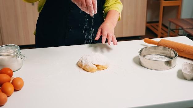Senior cheffrau, die weizenmehl für hausgemachtes brot verwendet. älterer bäcker im ruhestand mit knochen und gleichmäßigem besprühen, sieben, verteilen von zutaten auf teig, backen von hausgemachter pizza und keksen.