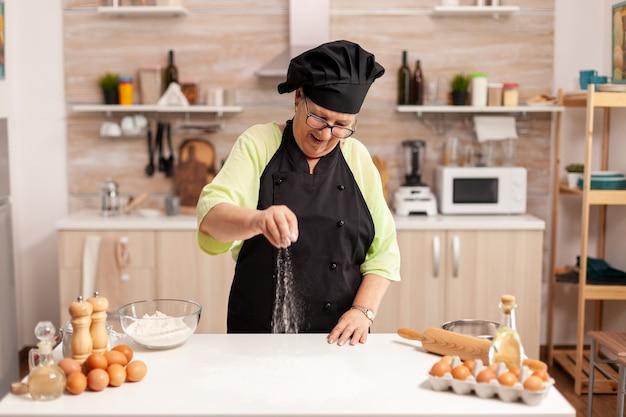 Senior dame chef lächelnd beim zubereiten von pizza bestreuen mehl auf küchentisch. glücklicher älterer koch mit gleichmäßigem besprühen, sieben und sieben von rohstoffen von hand.