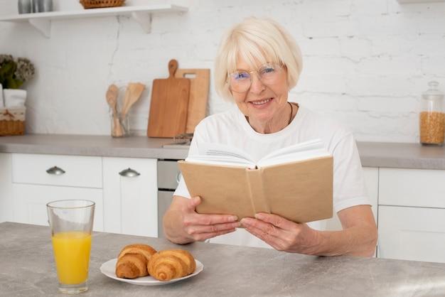 Senior, der ein buch in der küche hält