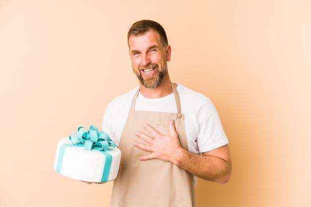 Senior, der einen kuchen an der beige wand hält, lacht laut und hält die hand auf der brust.