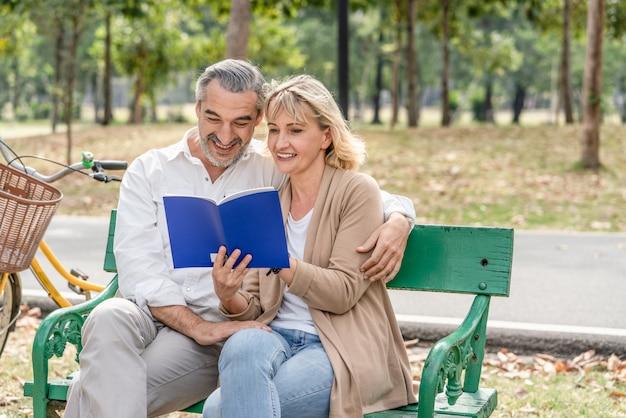 Senior des glücklichen paars, der zusammen ein buch bei der entspannung und beim sitzen auf der bank im park liest