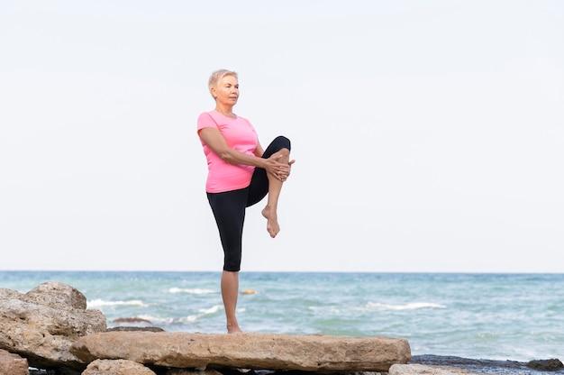 Senior fitness trainer nimmt an pilates-kursen im freien teil. gleichgewichtsübungen