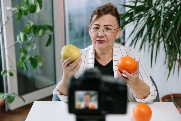 Senior frau food vlogger aufnahme video über gesunde ernährung. die ältere frau des lifestyle-bloggers bereitet ein neues video für ihren kanal vor und kommuniziert mit den followern.