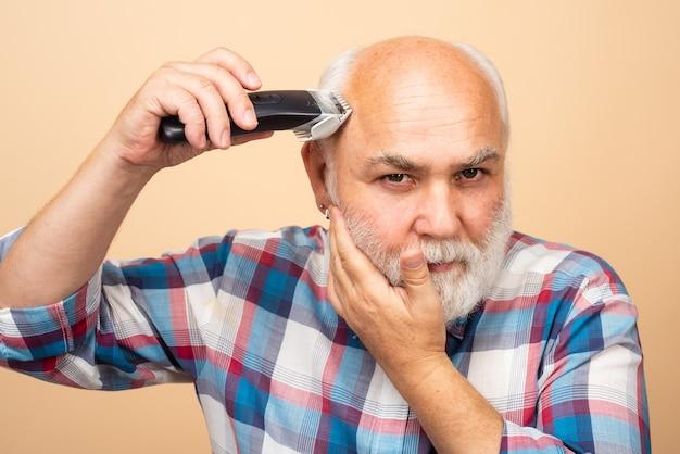 Senior friseur mann mit haarschneidemaschine, haarschnitt mit einem elektrorasierer. friseursalon konzept für friseursalons.
