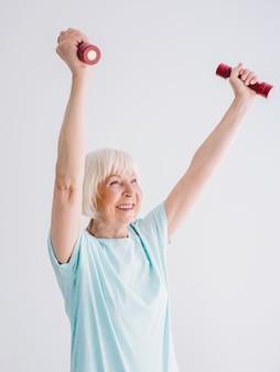 Senior fröhliche frau, die sport mit hanteln macht anti-age sport gesunder lebensstil
