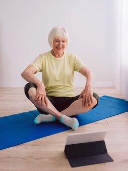 Senior fröhliche friedliche frau, die yoga indoor online macht anti-age-sport-technologie-yoga-konzept