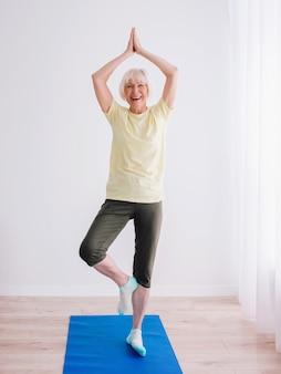 Senior fröhliche friedliche frau macht yoga indoor namaste hände anti-age-sport-yoga-konzept
