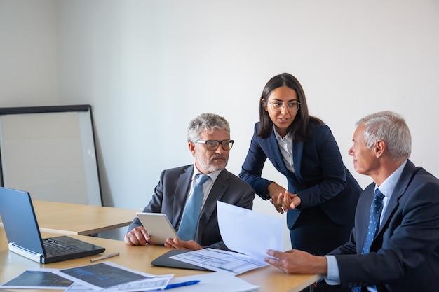 Senior geschäftsleute und junge assistentin arbeiten mit statistik. seriöse inhaltskollegen in büroanzügen sitzen am tisch mit laptop, dokumenten und tablet. management- und partnerschaftskonzept